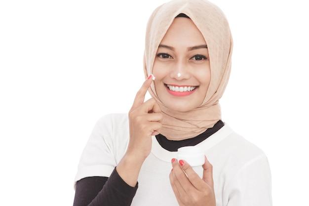 Bouchent le portrait de la belle femme asiatique à l'aide de crème hydratante pour la peau du visage
