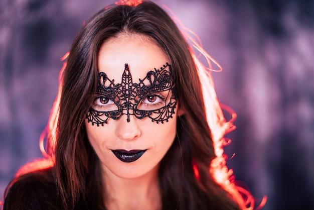 Bouchent le portrait d'une belle femme brune en costume de sorcière posant lors d'une fête d'halloween
