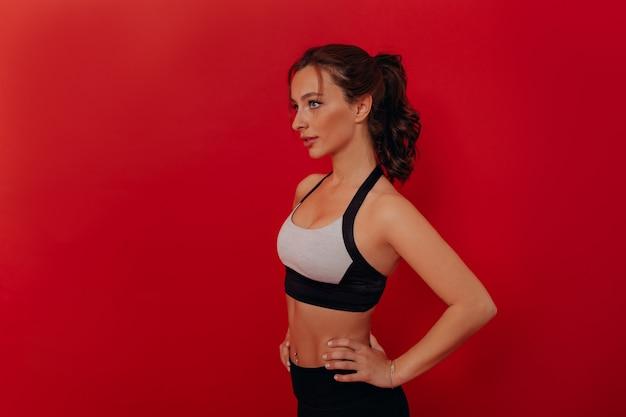 Bouchent le portrait de la belle femme brune portant haut de sport isolé sur mur rouge