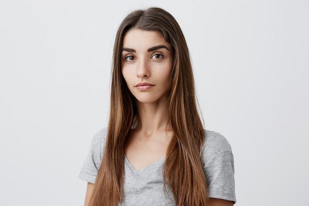 Bouchent le portrait de la belle femme caucasienne aux cheveux noirs sérieux avec une coiffure longue en chemise grise décontractée avec une expression de visage détendue et calme. santé et beauté.