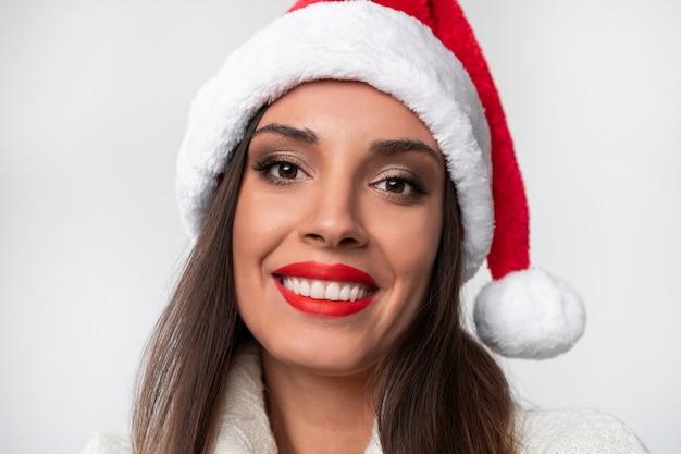 Bouchent portrait belle femme caucasienne en bonnet rouge sur mur blanc. concept de noël nouvel an. dents de femme mignonne souriant des émotions positives avec copie gratuite