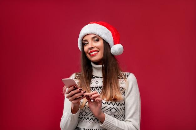 Bouchent portrait belle femme caucasienne en bonnet rouge sur mur rouge. concept de noël nouvel an. dents de femme mignonne souriant des émotions positives avec copie gratuite