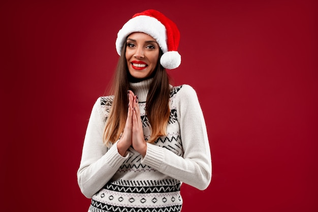 Bouchent portrait belle femme caucasienne en bonnet rouge sur mur rouge. concept de noël nouvel an. dents de femme mignonne souriant émotions positives avec copie libre espace namaste