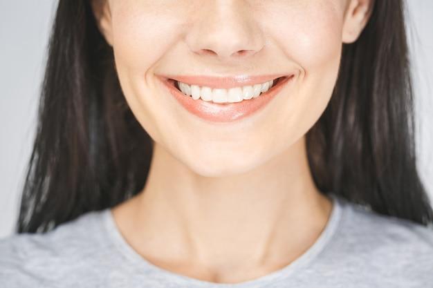 Bouchent le portrait de la belle femme joyeuse souriante, démontrant des dents blanches, regardant la caméra. expressions du visage, émotions et langage corporel.