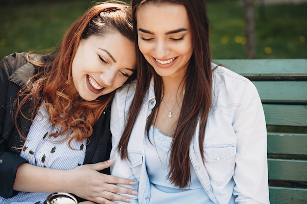 Bouchent le portrait d'une belle femme taille plus aux cheveux rouges s'amusant à rire les yeux fermés tout en se penchant la tête sur son amie assise sur un banc.