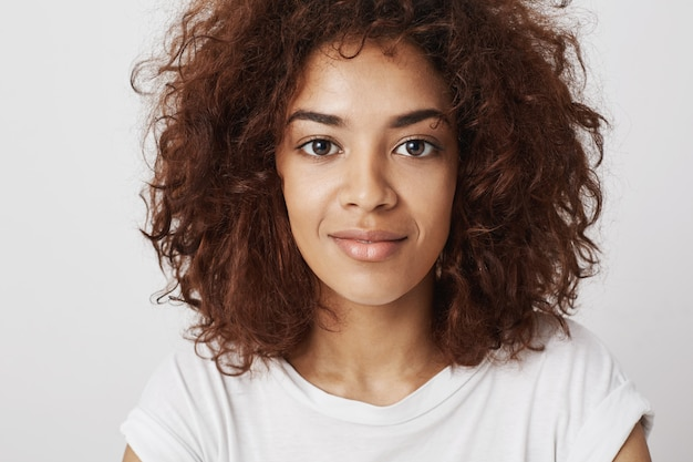 Bouchent le portrait de la belle fille africaine avec de grands yeux souriant avec un sourire confiant et calme, convaincant et attrayant.