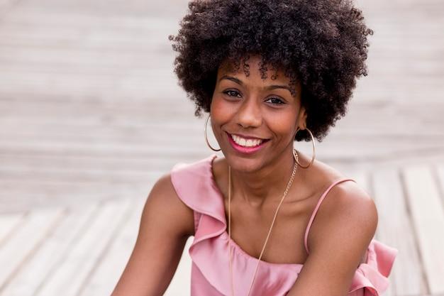 Bouchent le portrait d'une belle jeune femme afro-américaine heureuse assis sur le plancher en bois et souriant. saison de printemps ou d'été. vêtements décontractés