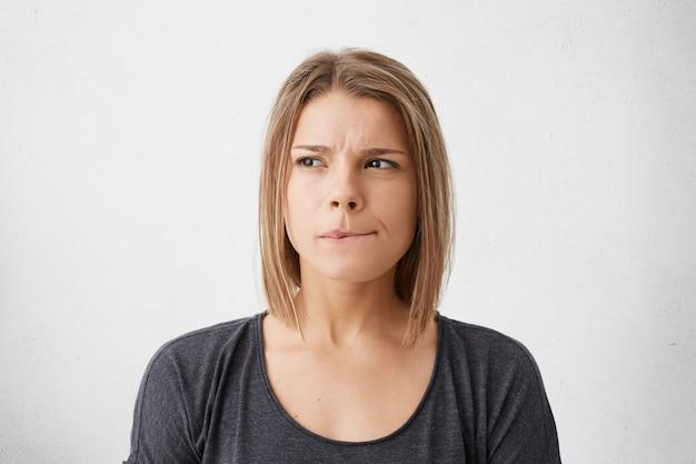 Bouchent le portrait de la belle jeune femme avec une coiffure bob se mordant les lèvres et regardant de côté avec une expression douteuse réfléchie car elle doit prendre une décision importante, posant au mur blanc