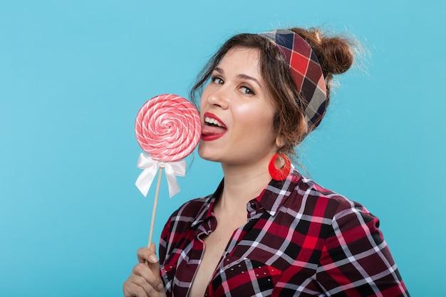 Bouchent le portrait de la belle jeune femme mangeant une sucette sur une surface bleue