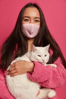 Bouchent le portrait de la belle jeune femme avec un masque de protection tenant un chat isolé