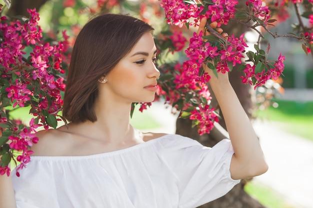 Bouchent le portrait de la belle jeune femme avec une peau lisse parfaite. dame séduisante en fleurs. portrait du visage de la belle femme.