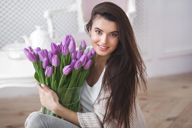Bouchent le portrait de la belle jeune femme tenant des fleurs. jolie femme aux tulipes