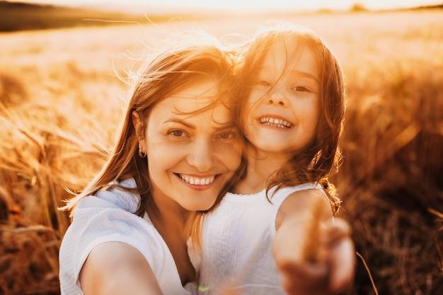 Bouchent le portrait d'une belle jeune mère embrassant sa fille et regardant la caméra en riant contre le coucher du soleil dans le champ de blé.