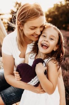 Bouchent le portrait d'une belle mère et fille embrassant et riant tout en regardant la caméra contre le coucher du soleil dans un champ de fleurs.