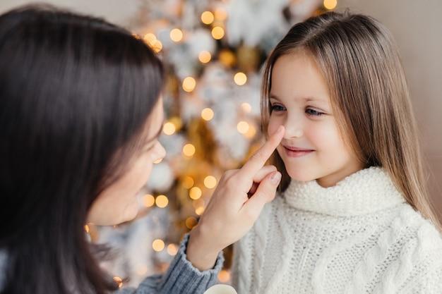 Bouchent le portrait de la belle petite fille aux cheveux longs, s'amuse avec sa mère, regarde dans les yeux, montez la tête contre un sapin décoré avec des guirlandes et des lumières. concept de célébration