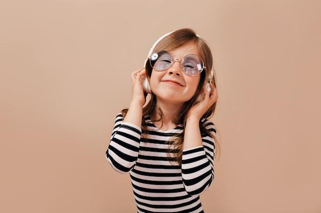 Bouchent le portrait de charmante jolie fille portant un t-shirt dépouillé à l'écoute de la musique avec un sourire heureux et les yeux fermés