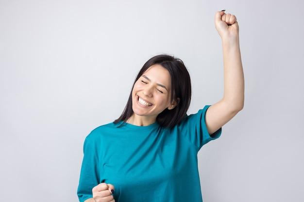 Bouchent le portrait de cris attrayants en gagnant souriant avec les poings levés jeune elle sa fille