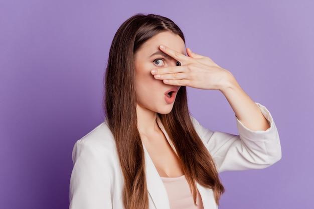 Bouchent le portrait de dame cacher les yeux peek porter un costume formel posant sur un mur violet
