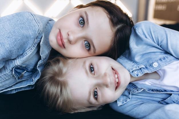 Bouchent le portrait de deux adorables filles caucasiennes se font face en jeans