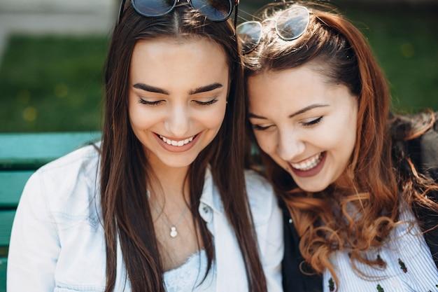 Bouchent le portrait de deux belle petite amie regardant un smartphone en riant alors qu'il était assis sur un banc à l'extérieur.