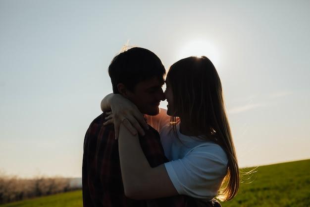 Bouchent le portrait de deux heureux amoureux se regardant et souriant sur le coucher du soleil.