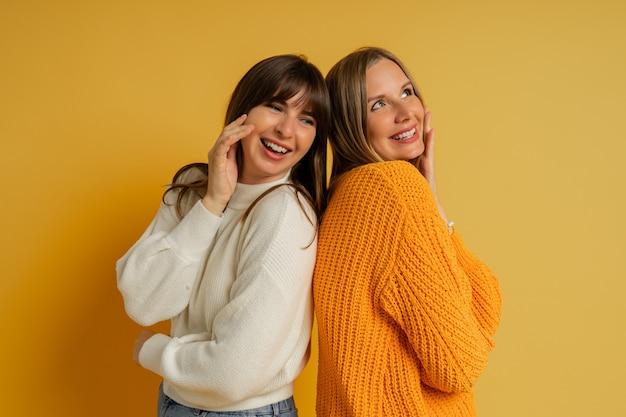 Bouchent le portrait de deux jolies femmes en pulls confortables posant sur jaune. tendances mode automne et hiver.