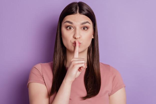 Bouchent le portrait d'un doigt de jolie fille couvrant les lèvres chut garder un complot secret isolé sur fond de couleur violette