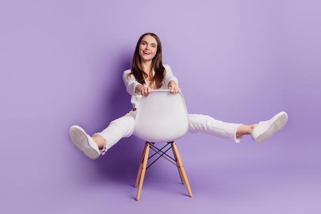 Bouchent Le Portrait D'une Drôle De Jeune Femme Insouciante Assise Sur Une Chaise Faisant Semblant D'équitation Posant Sur Un Mur Violet Photo Premium