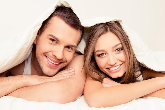 Bouchent le portrait du joli homme et femme couchée sous une couverture