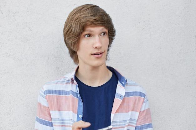 Bouchent portrait d'écolier à la mode avec une coiffure à la mode en regardant avec une expression surprise de côté tenant un téléphone intelligent
