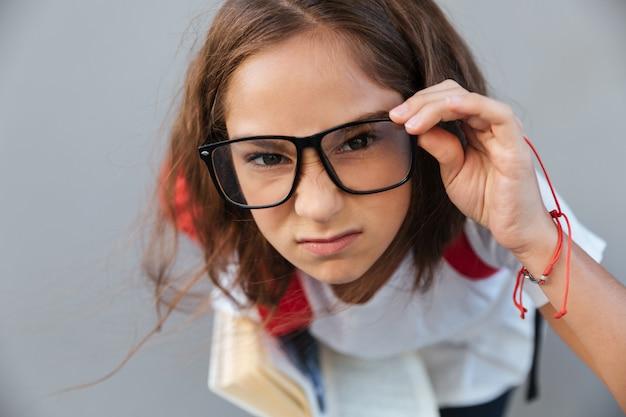 Bouchent portrait d'écolière brune sérieuse à lunettes