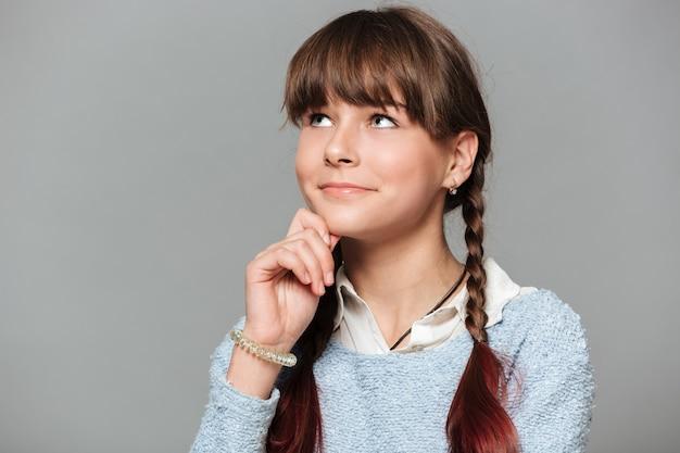 Bouchent le portrait d'une écolière souriante réfléchie
