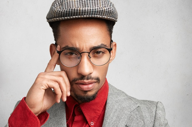 Bouchent le portrait d'un entrepreneur masculin sérieux à la peau sombre porte une casquette à la mode