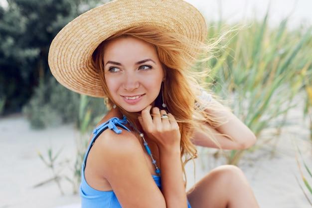 Bouchent le portrait d'été de la belle femme joyeuse au chapeau de paille reposant sur la plage ensoleillée en vacances. ambiance tropicale.