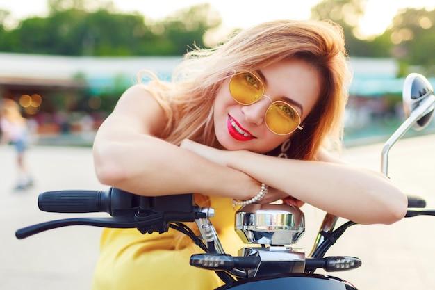 Bouchent le portrait d'été de femme joyeuse tête rouge dans des lunettes de soleil jaunes élégantes équitation scooter électro dans la ville moderne ensoleillée. accessoires tendance.