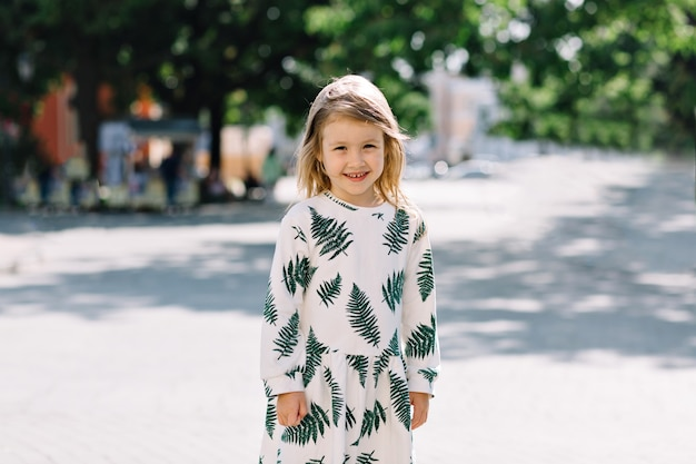 Bouchent le portrait extérieur de la jolie petite fille souriante en robe d'été avec un sourire merveilleux s'amusant et regardant à l'avant