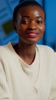Bouchent le portrait d'une femme africaine d'affaires souriant à la caméra