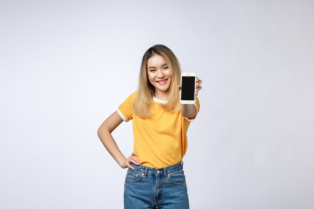 Bouchent le portrait d'une femme asiatique souriante montrant un écran blanc mobile