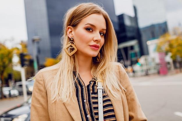 Bouchent le portrait d'une femme blonde élégante avec des boucles d'oreilles élégantes. dame élégante bénéficiant de loisirs près du centre commercial dans une grande ville moderne.