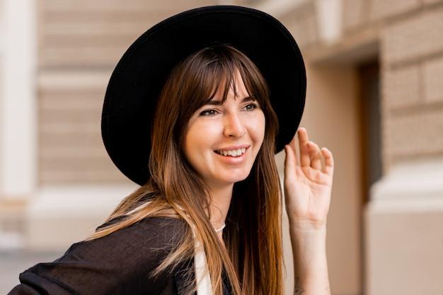 Bouchent le portrait d'une femme brune élégante en tenue décontractée et chapeau noir. profiter des vacances dans la ville européenne