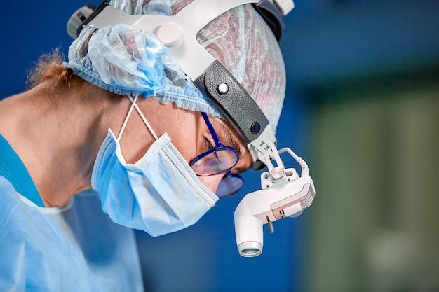Bouchent portrait de femme chirurgien médecin portant un masque de protection et un chapeau pendant l'opération. soins de santé, éducation médicale, concept de chirurgie.
