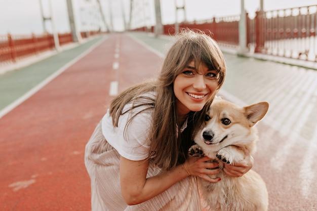 Bouchent le portrait d'une femme heureuse aux cheveux longs posant avec son chien à l'extérieur