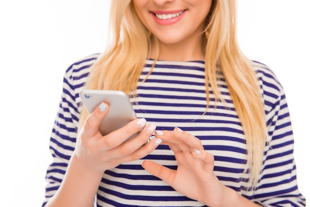 Bouchent le portrait d'une femme heureuse en tapant des sms sur son smartphone