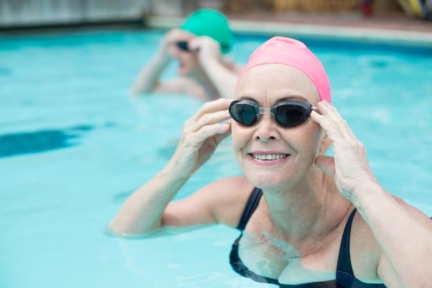 Bouchent le portrait de femme mûre nageant dans la piscine