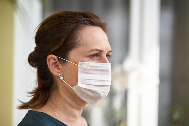 Bouchent le portrait de femme portant un masque chirurgical à cause des virus et de la pollution de l'air.