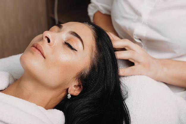 Bouchent le portrait d'une femme de race blanche aux cheveux noirs allongé sur le canapé au cours d'une procédure de massage de la tête