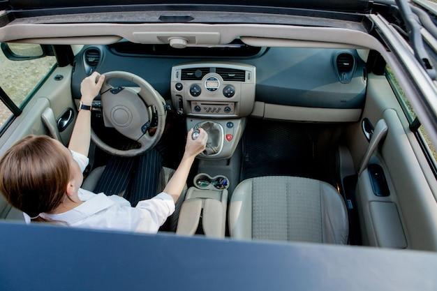 Bouchent le portrait d une femme à la recherche agréable avec une expression positive heureuse, se contentant d un voyage inoubliable en voiture, est assis sur le siège du conducteur. personnes, conduite, concept de transport