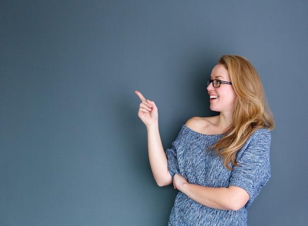 Bouchent le portrait d'une femme souriante, pointant le doigt sur fond gris