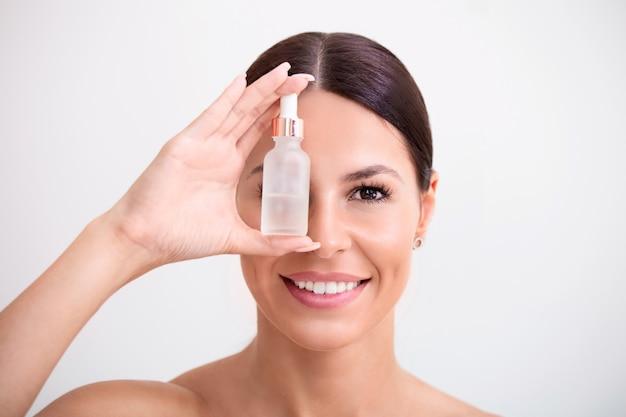 Bouchent le portrait de femme souriante tenant une bouteille de sérum pour le visage.