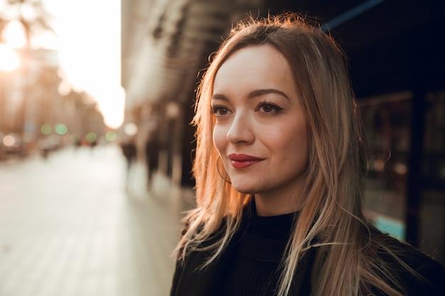 Bouchent le portrait d'une fille blonde à barcelone au coucher du soleil